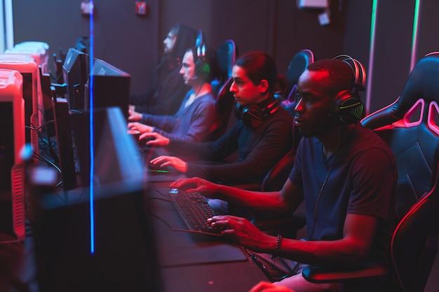 Онлайн геймеры играют в стратегические игры в компьютерном клубе