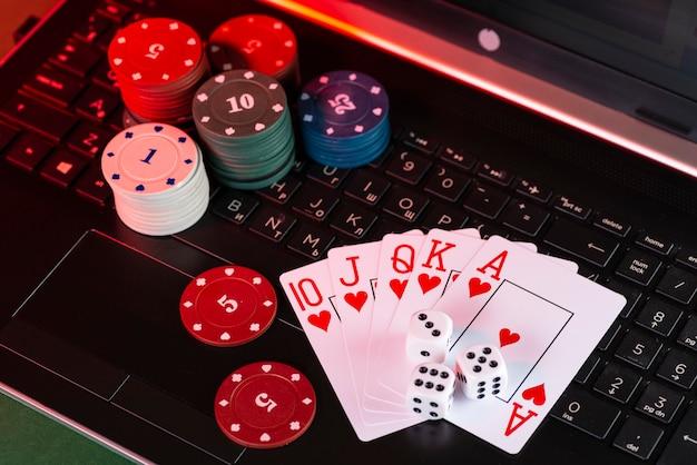 オンラインゲームプラットフォーム、カジノ、ギャンブルビジネス。ノートパソコンのキーボードのカード、サイコロ、マルチカラーのゲームピース