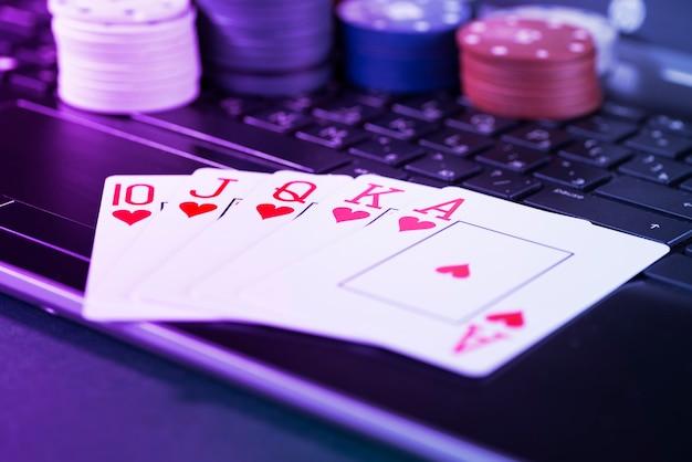 オンラインゲームプラットフォーム、カジノ、ギャンブルビジネス。ノートパソコンのキーボードのカード、サイコロ、マルチカラーのゲームピース。