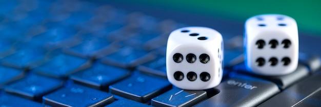オンラインゲームプラットフォーム、カジノ、ギャンブルビジネス。緑の背景のラップトップキーボードのサイコロ。
