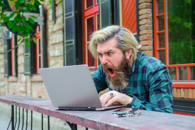 Победа в онлайн-играх онлайн возбужденный мужчина с ноутбуком на открытом воздухе онлайн-работа цифровая работа фриланс
