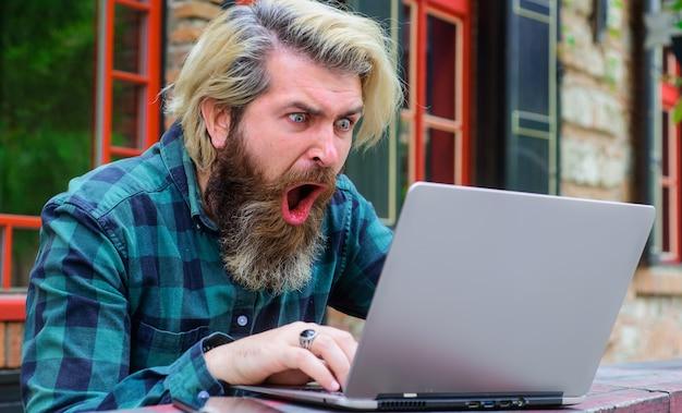 Онлайн-игры. победа в сети. онлайн работа. возбужденный бородатый мужчина с ноутбуком на открытом воздухе. внештатный.