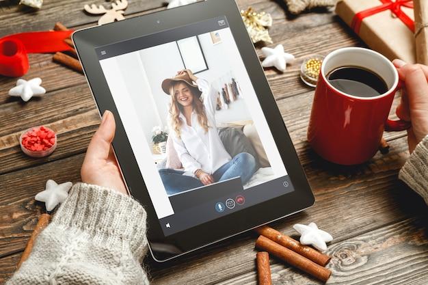 Интернет-приветствие с рождественским цифровым планшетом в руке