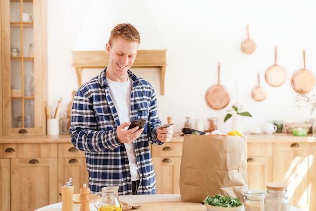 Покупки продуктов в интернете мужчина с помощью кредитной карты и телефона оплачивает продукты питания, стоя на кухне дома.