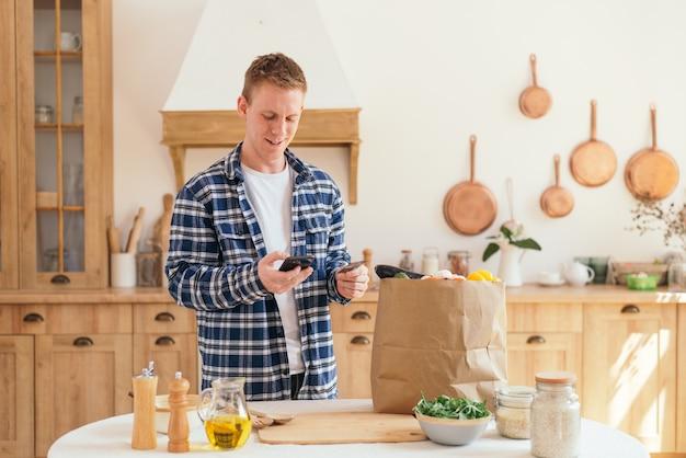Покупки продуктов в интернете: мужчина оплачивает продукты питания с помощью кредитной карты и телефона.
