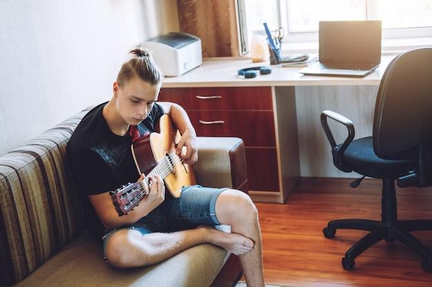 オンラインギターレッスン。ギターを弾く白人のティーンエイジャー、オンラインギターレッスン、好きな趣味、レジャーを楽しんでいます。 10代のギターの選び方。初心者のためのアコースティックギター。
