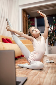 Интернет-хобби, фитнес, дистанционное обучение. молодая балерина занимается классической хореографией во время онлайн-урока балета дома перед ноутбуком, онлайн-образование