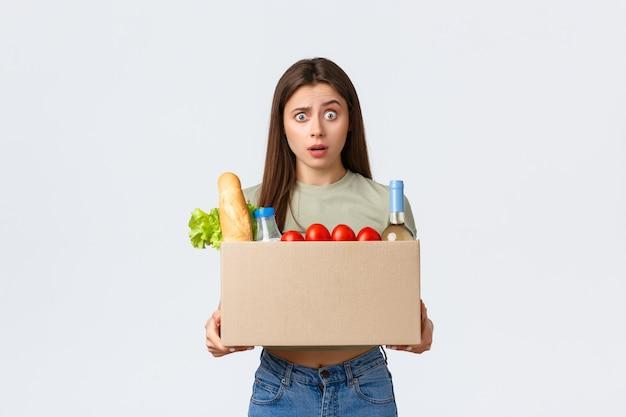 オンライン宅配、インターネット注文、食料品の買い物のコンセプト。彼女の注文で箱を保持している混乱した女性、間違った食料品製品を受け取り、困惑したカメラ、白い背景を見つめる