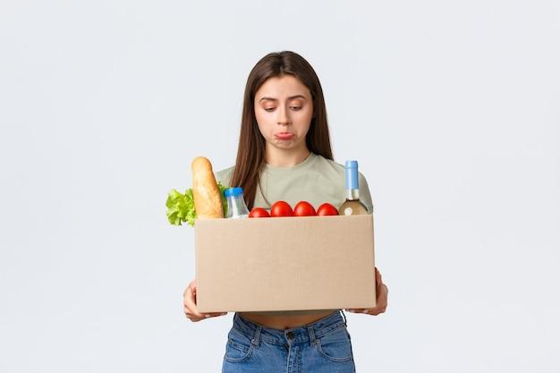 オンライン宅配、インターネット注文、食料品の買い物のコンセプト。失望した女性の顧客は、間違った食料品の注文を受け取り、箱の中で動揺してふくれっ面を見て、白い背景に立っています。