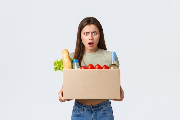 オンライン宅配、インターネット注文、食料品の買い物のコンセプト。狂ったと欲求不満の女性は、食料品の間違った注文を受け取り、製品の入った箱のように眉をひそめ、白い背景に立っています。