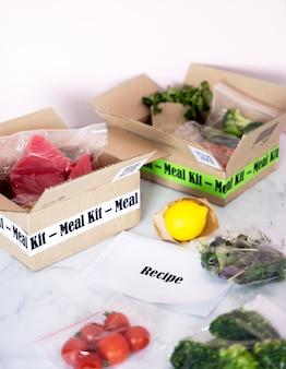 온라인 가정 음식 배달. 포장된 참치, 새우, 야채, 조리법 카드가 있는 크래프트 상자는 부엌 배경에 있습니다. 코로나바이러스 전염병 및 사회적 거리두기 기간 동안 음식 배달 서비스.