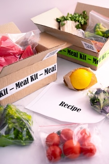 Online home food delivery. craft box with packed tuna, shrimp, vegetables and recipe card on a kitchen background. food delivery services during coronavirus pandemic and social distancing.