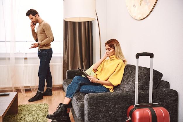 온라인 호텔 조사. 젊은 남자는 스마트폰으로 호텔 안내원과 논쟁합니다. 젊은 여성이 디지털 태블릿에서 새 호텔을 찾고 있다
