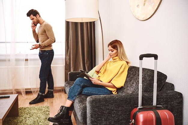 Online hotel research. young man argue with hotel receptionist by smartphone. young woman is searching for a new hotels at digital tablet