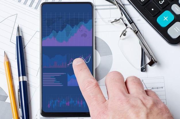 온라인 투자. 한 남자가 차트와 그래프가있는 모바일 앱이있는 스마트 폰을 들고 있습니다.