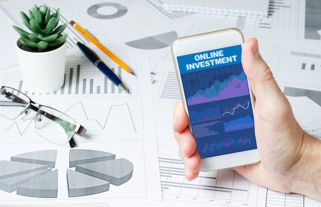 Online investment. a man is holding a smartphone with a mobile app with charts and graphs. copy space.