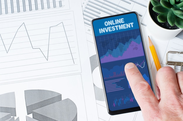 Online investment. a man is holding a smartphone with a mobile app with charts and graphs