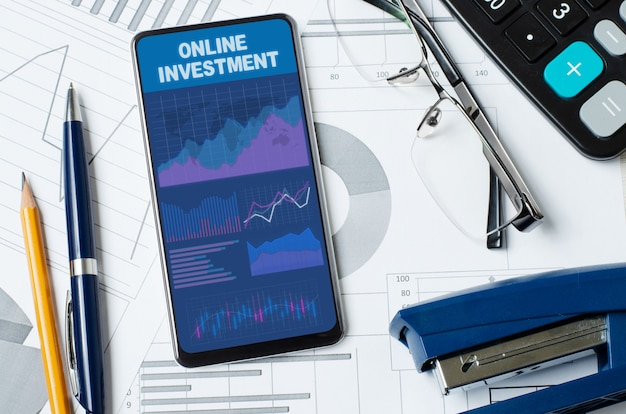 Online investment. smartphone with a mobile app on the background of graphs and charts.