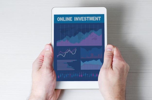 온라인 투자. 남자의 손에 그래프와 다이어그램 태블릿.