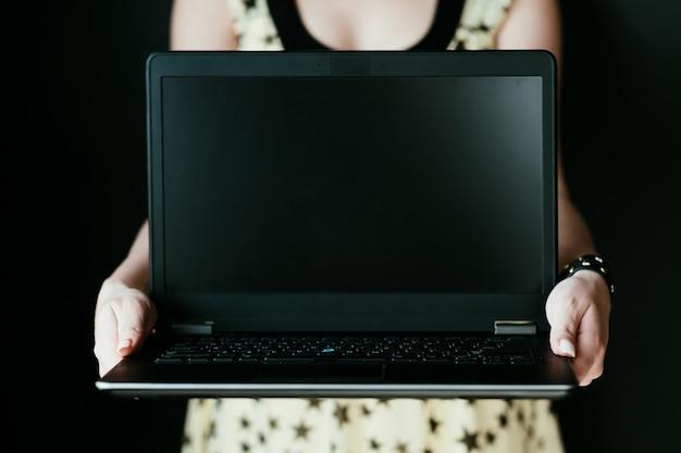 온라인 it 교육 및 소프트웨어 개발. 인터넷에서 새로운 직업을 배우십시오. 프로그래머 코더 또는 웹 개발자가됩니다. 빈 검은 화면으로 노트북을 들고 여자입니다.