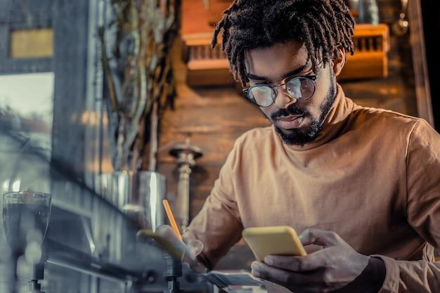 Работа онлайн. красивый бородатый мужчина склоняет голову, глядя на экран своего гаджета