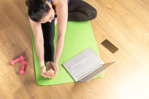 온라인 노트북 요가 홈. 노트북과 요가 매트에서 요가 연습하는 여자의 최고 볼 수 있습니다. 중간 나이 든 여자는 집에서 비디오 훈련으로 명상과 휴식을 취하고 있습니다.