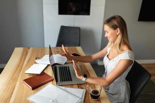 온라인 학습 및 작업. 화상 통화, 실내에서 다른 사람들과의 화상 회의. 홈 오피스에서 작업하는 노트북 컴퓨터와 여자