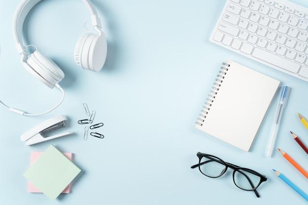 온라인 학습 디자인 개념입니다. 파란색 테이블 배경에 컴퓨터, 헤드폰, 문구류가 있는 학생 테이블의 맨 위 보기.