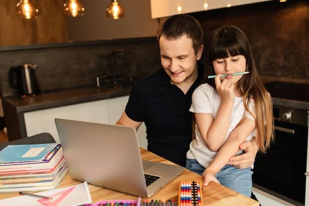 온라인 학습. 숙제를하면서 가족 관계. 아버지는 딸이 집에서 온라인 수업을 할 수 있도록 도와줍니다.