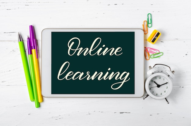 온라인 학습-태블릿에 필기 비문. 어린이를위한 원격 훈련의 개념. 흰색 나무 바탕에 태블릿 및 사무 용품.