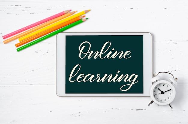 온라인 학습 - 태블릿에 손으로 쓴 비문. 어린이를 위한 원격 훈련의 개념입니다. 흰색 나무 바탕에 태블릿과 사무용품이 있습니다.