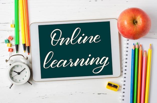 Онлайн-обучение - рукописная надпись на планшете. концепция дистанционного обучения детей. таблетка и канцелярские товары на белом фоне деревянных.