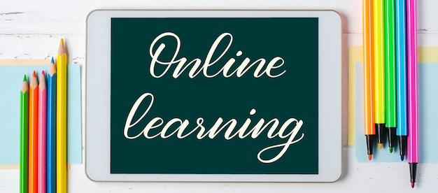 온라인 학습-태블릿에 필기 비문. 어린이를위한 원격 교육의 개념. 흰색 나무 배경에 태블릿 및 사무 용품.