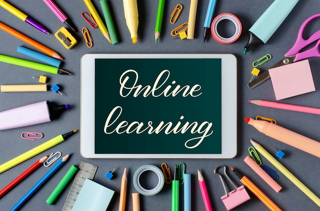 Online learning - handwritten inscription on a tablet. the concept of distance training for children. tablet and office supplies on a dark background.