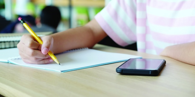 Online learning home school concept, close up of college student hand writing notebook and smartphone on table, college education and communication in campus, home school online education, e learning