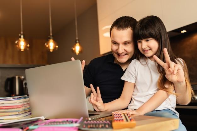 オンライン学習。女子高生と彼女の父親の自宅、オンラインレッスン、ラップトップでのビデオ通話。遠隔教育、ホームスクール。家族の一体感