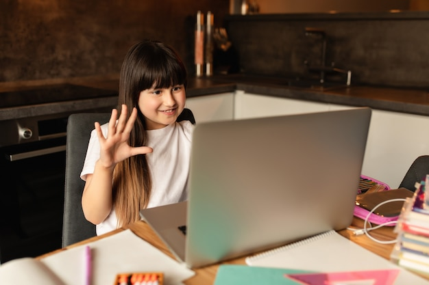Online learning. schoolgirl learns using video call on laptop