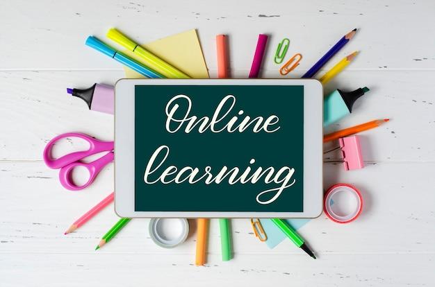 白い木製の背景の円の周りに学用品とipadのオンライン学習テキスト