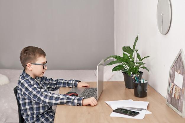 自宅でのオンラインレッスン、隔離期間中の社会的距離、自己分離、オンライン教育の概念、家庭教師。ラップトップを使用してオンラインで言語を学習する少年、遠隔教育。学生少年、学校