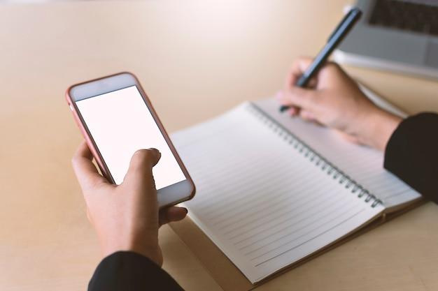 Интернет-маркетологи поднимают дисплей мобильных устройств белый экран с золотым фоном боке