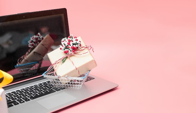 Online marketing, krismas concept laptop with gifts, on pink background, banner, copy space