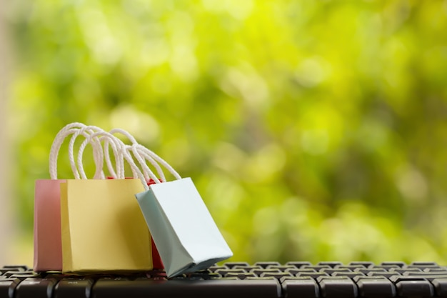 Онлайн маркетинг / концепция оплаты: хозяйственные сумки со смартфонами на клавиатуре компьютера, онлайн-магазины значков и социальные сети. изображает потребительские покупки товаров, товаров и услуг из интернета