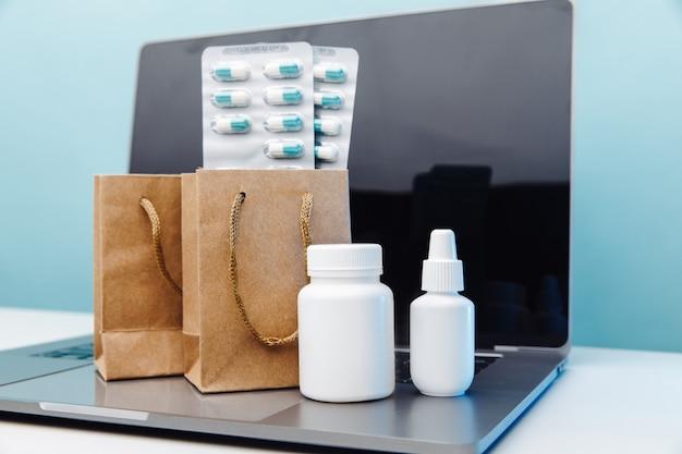ノート パソコンに薬と錠剤とコンテナーが入ったオンライン医療ショッピング コンセプトの紙袋