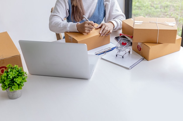 オンラインマーチャントは、小包ボックスの前面に顧客の配送情報を書き込み、小包ボックスに商品を梱包して、民間の運送会社に発送しています。オンラインショッピングのコンセプト