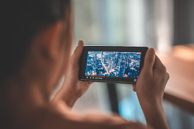 スマートフォンでのオンライン映画ストリーム。架空のビデオプレーヤーサービスと携帯電話で映画を見ている女性。