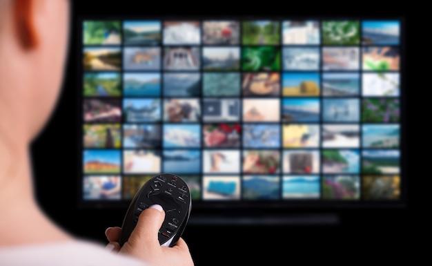 Интернет-концепция мультимедийного видео на телевизоре в темной комнате. женщина смотрит онлайн-телевидение с пультом дистанционного управления в руке. экран службы vod. экран телевизора с множеством картинок