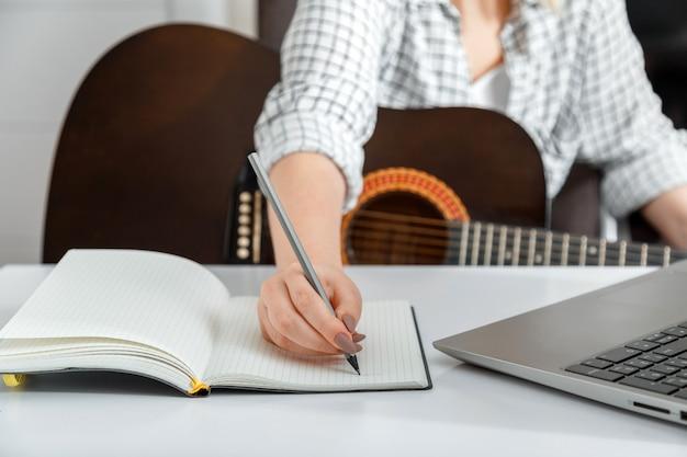 オンラインミュージカルギターe教育。自宅でギターを弾くためのオンライントレーニングクラス。ラップトップを介してアコースティックギターを練習しているミュージシャン。ビデオレッスン中にノートに曲を書く女性。