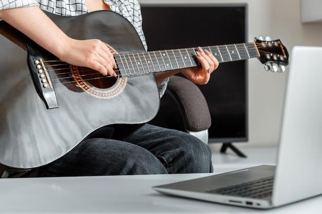 オンラインミュージカルギター演奏。若い女性はラップトップでオンラインオーディエンスのために自宅でアコースティックギターを演奏します。ビデオコンサートまたはオンラインクラスは、ロックダウン中のギタートレーニング音楽と教育をコースします。