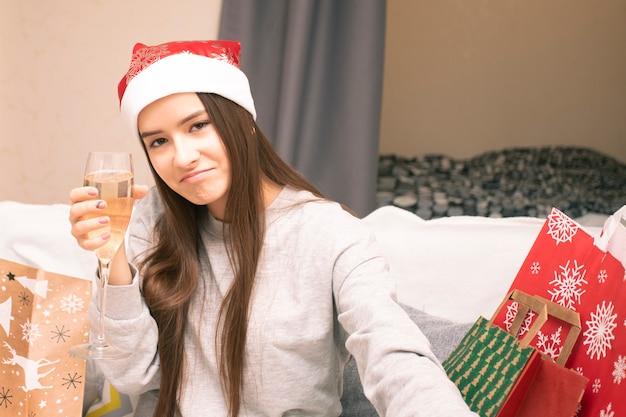 オンラインの新年とクリスマスの挨拶。サンタの帽子をかぶった女の子が、シャンパングラスを使ってビデオリンクを介して家族や友人に電話をかけます