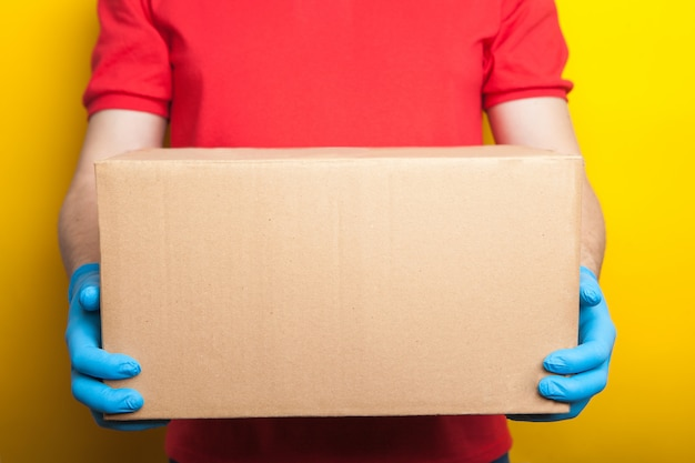 Online ordering and delivery. a man in a red uniform and rubber medical gloves holds a box on a bright yellow background. food delivery during the coronavirus quarantine period.